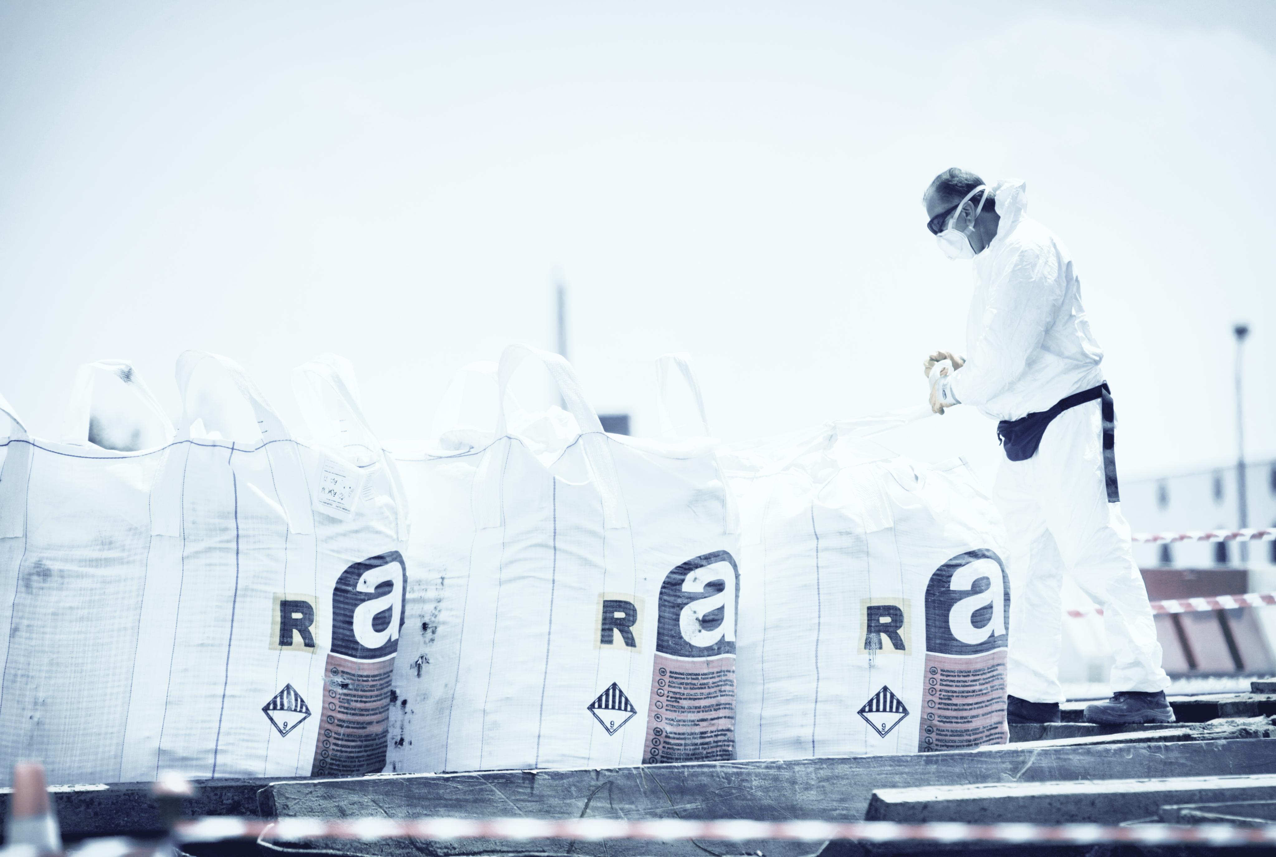 Photo d'un travailleur manipulant des sacs de déchets d'amiante